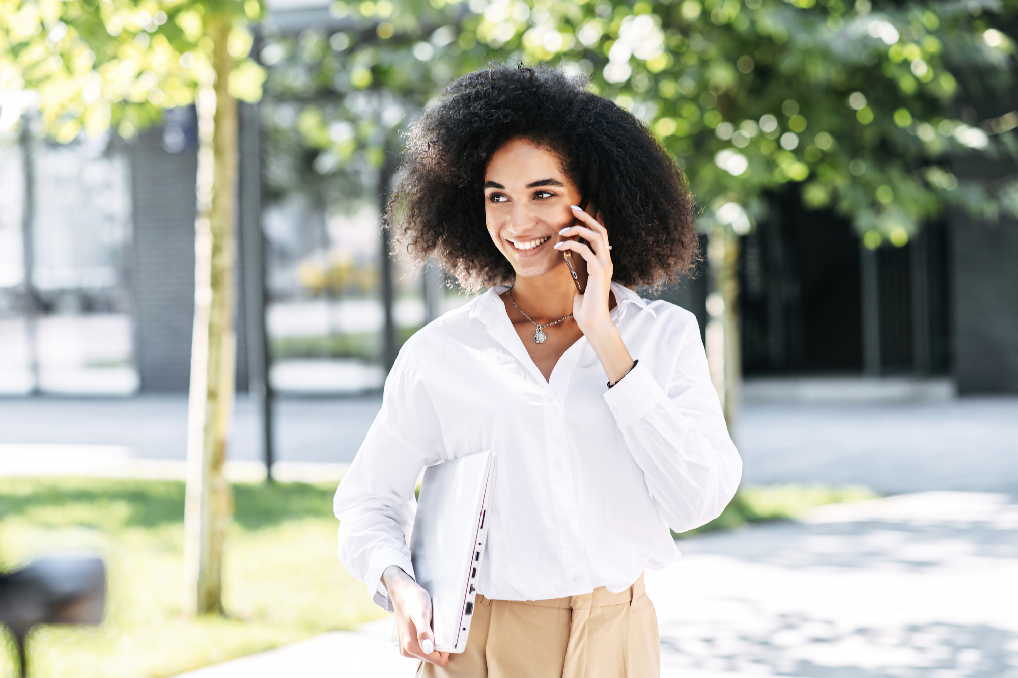 A woman is talking on the phone outdoors