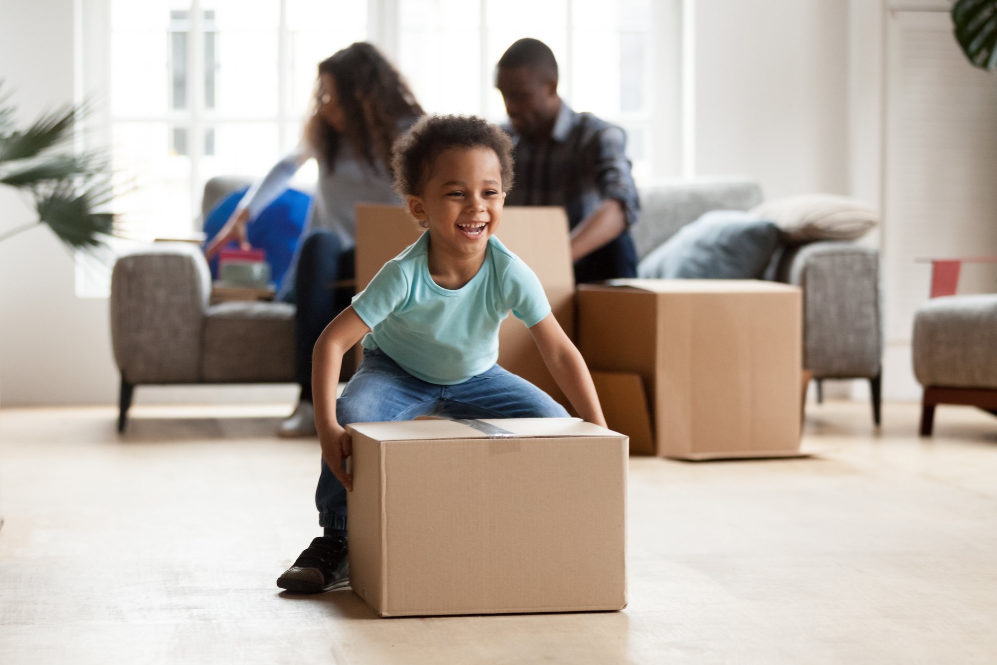 Adorable little boy playing with cardboard box at home