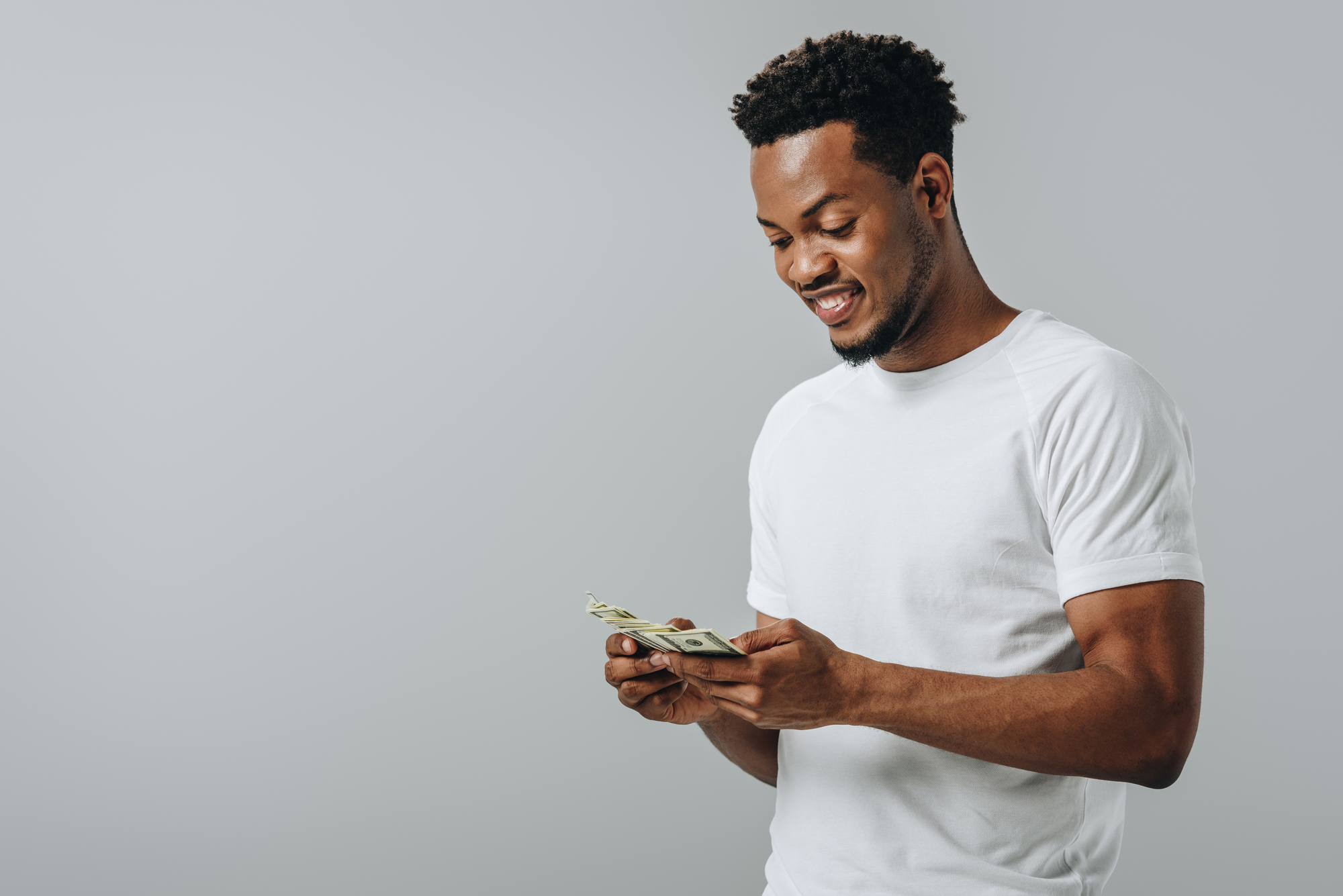 African American man counting dollar banknotes isolated on grey
