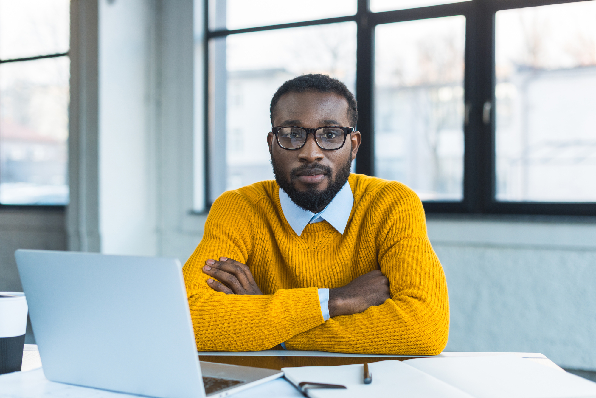 African american businessman sitting with crossed arms and looking at camera in office
