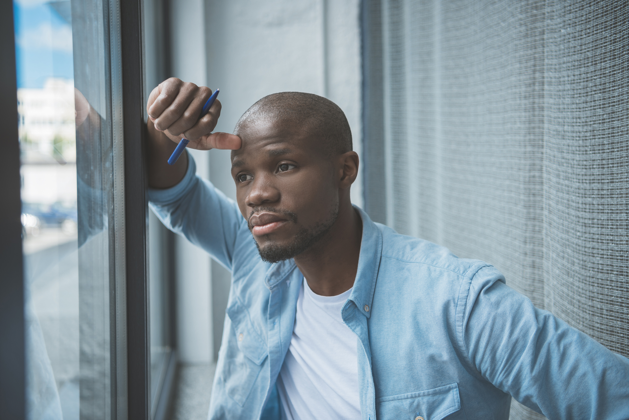 African american man looking at window