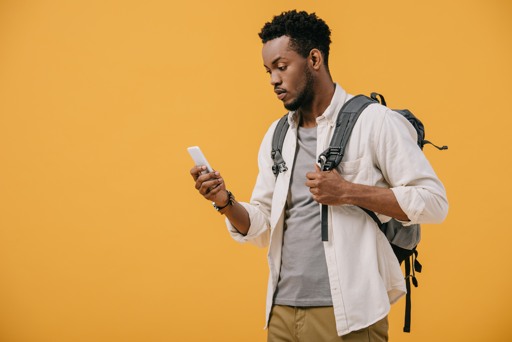 African american man with backpack looking at smartphone isolated on orange