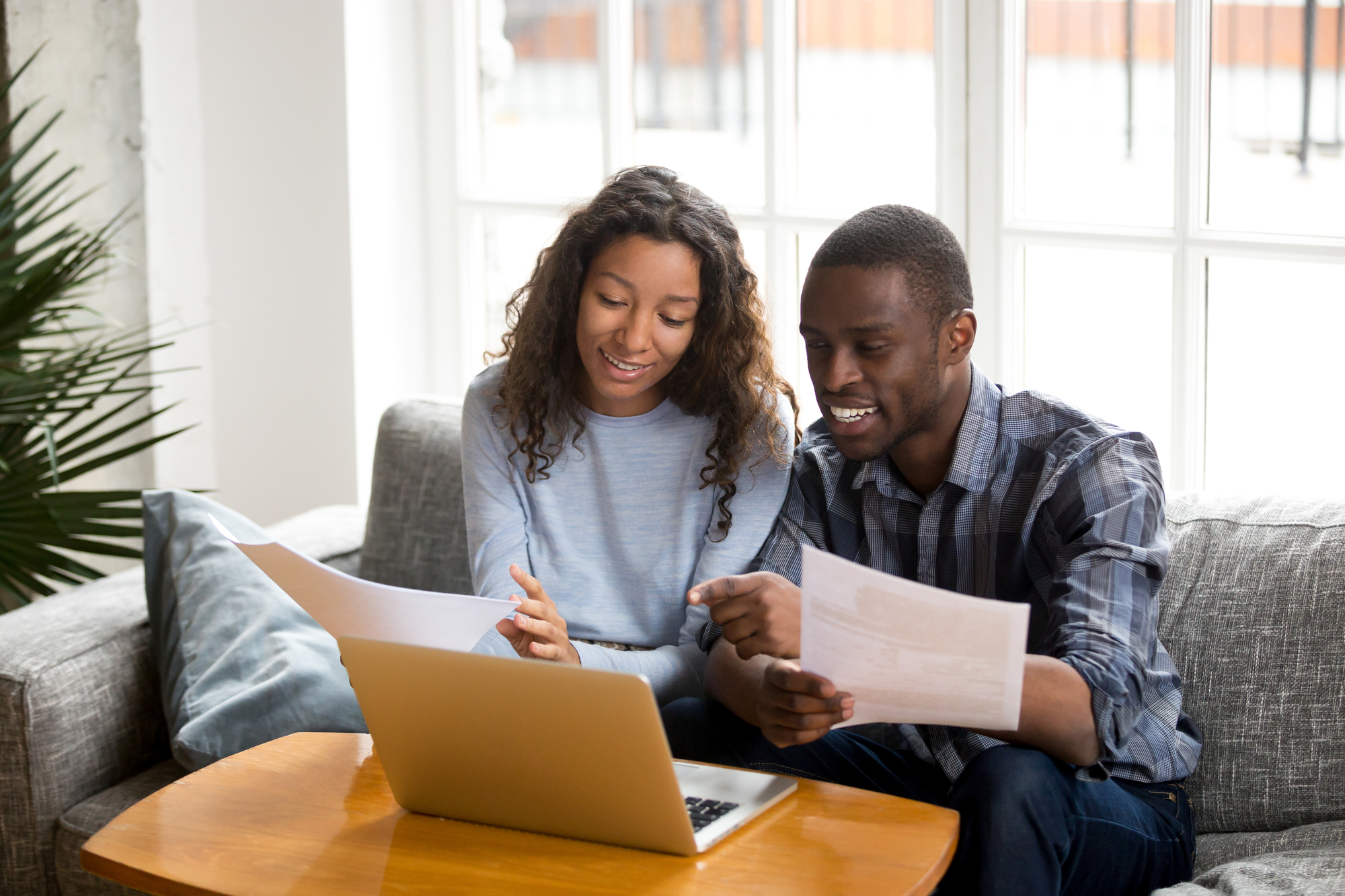 African black positive married couple sitting on sofa at home read documents paper checking bills, bank account balance feeling satisfied and happy