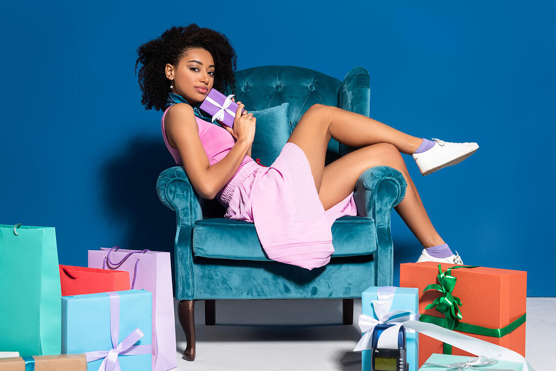 Beautiful african american woman sitting in velour armchair near payment terminal with check, shopping bags and gifts
