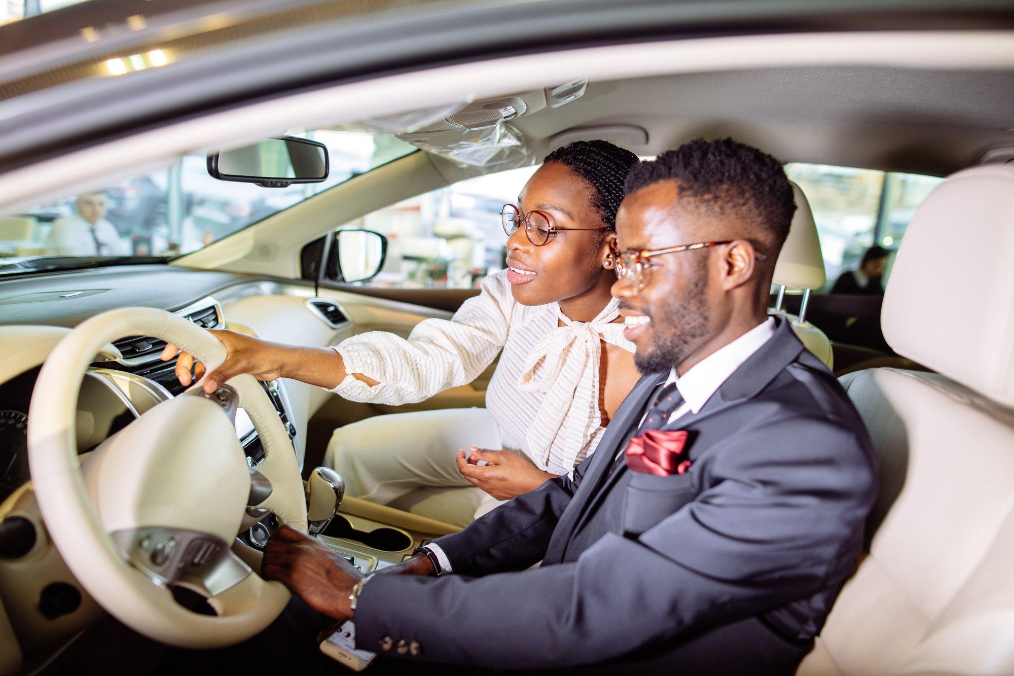 Beautiful african couple is choosing new car at dealership