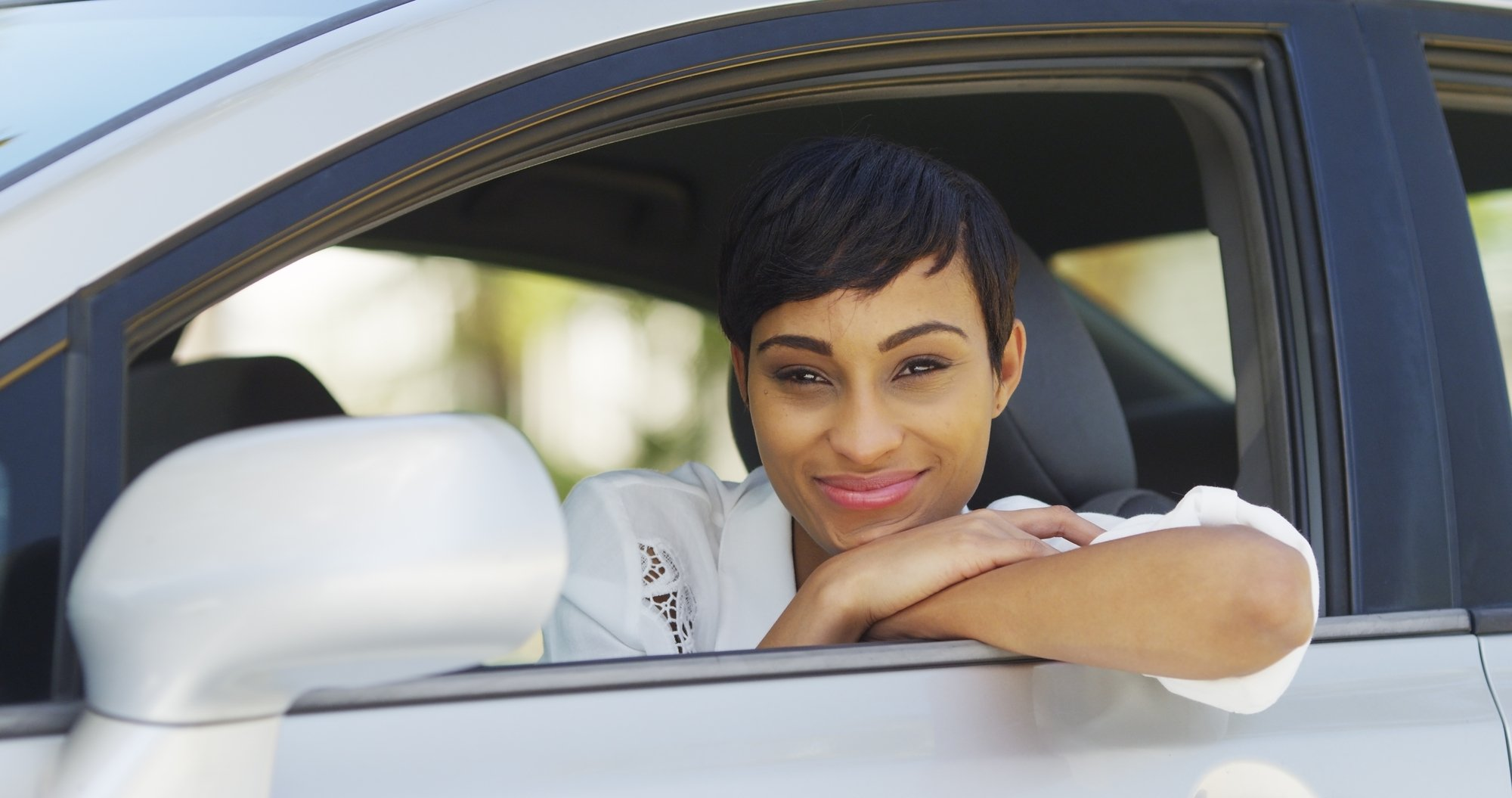 Black woman smiling and looking out of car window