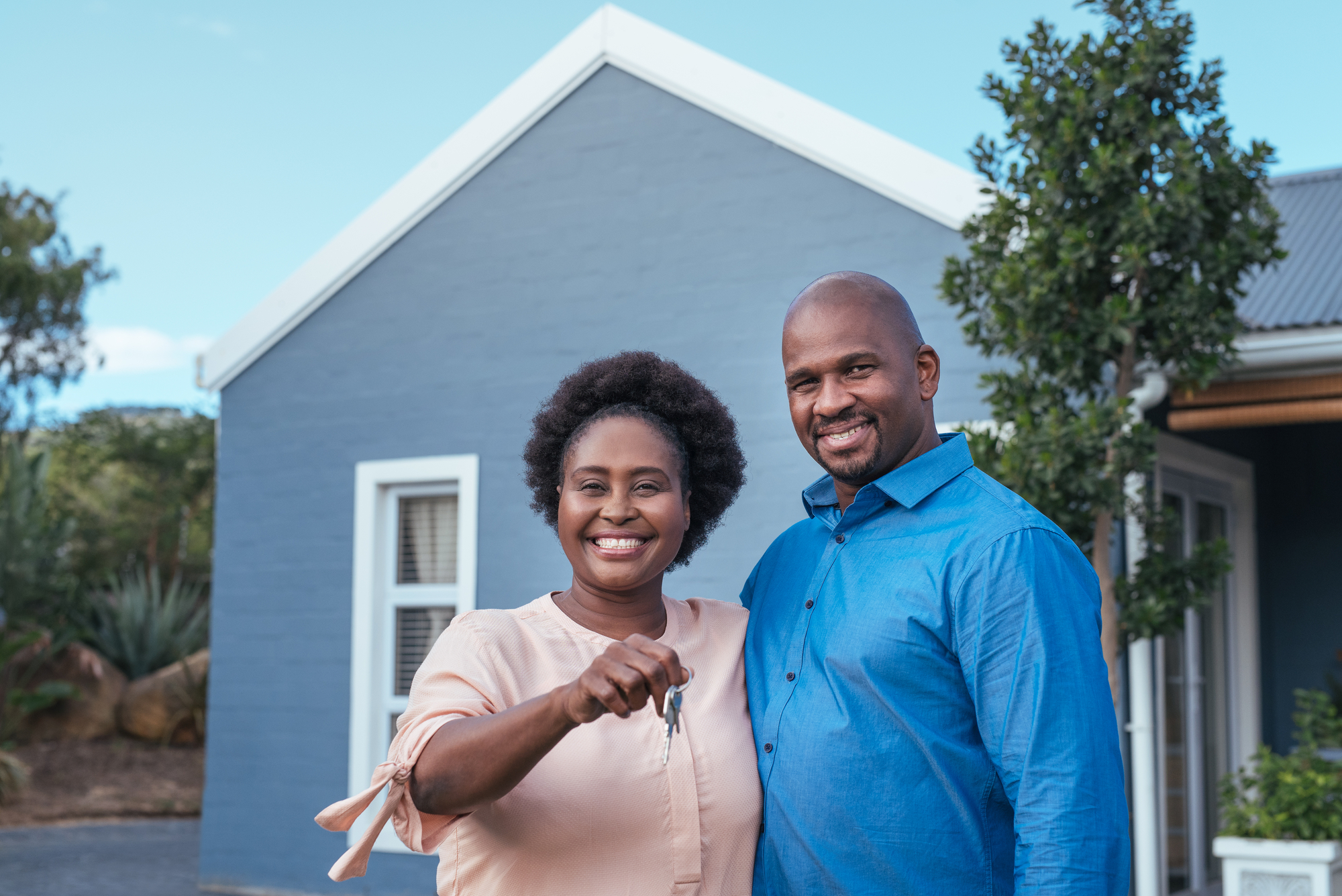 Couple standing with keys to new home