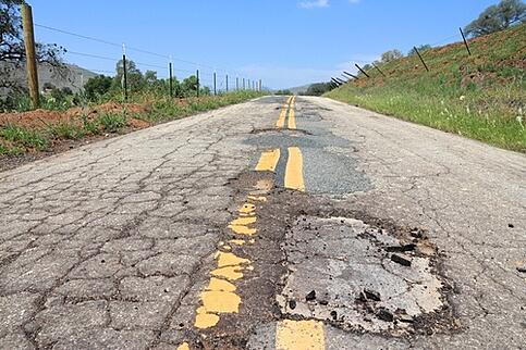 Road with multiple potholes.