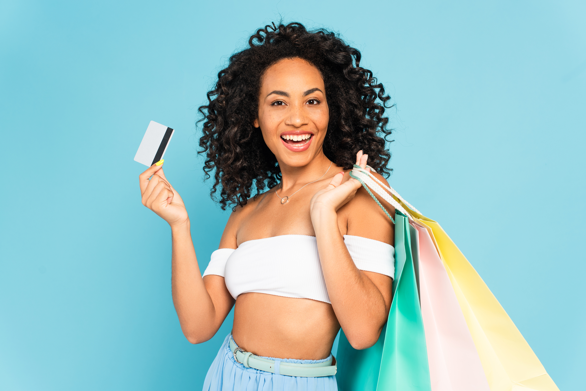 Excited african american woman holding credit card and shopping bags isolated on blue