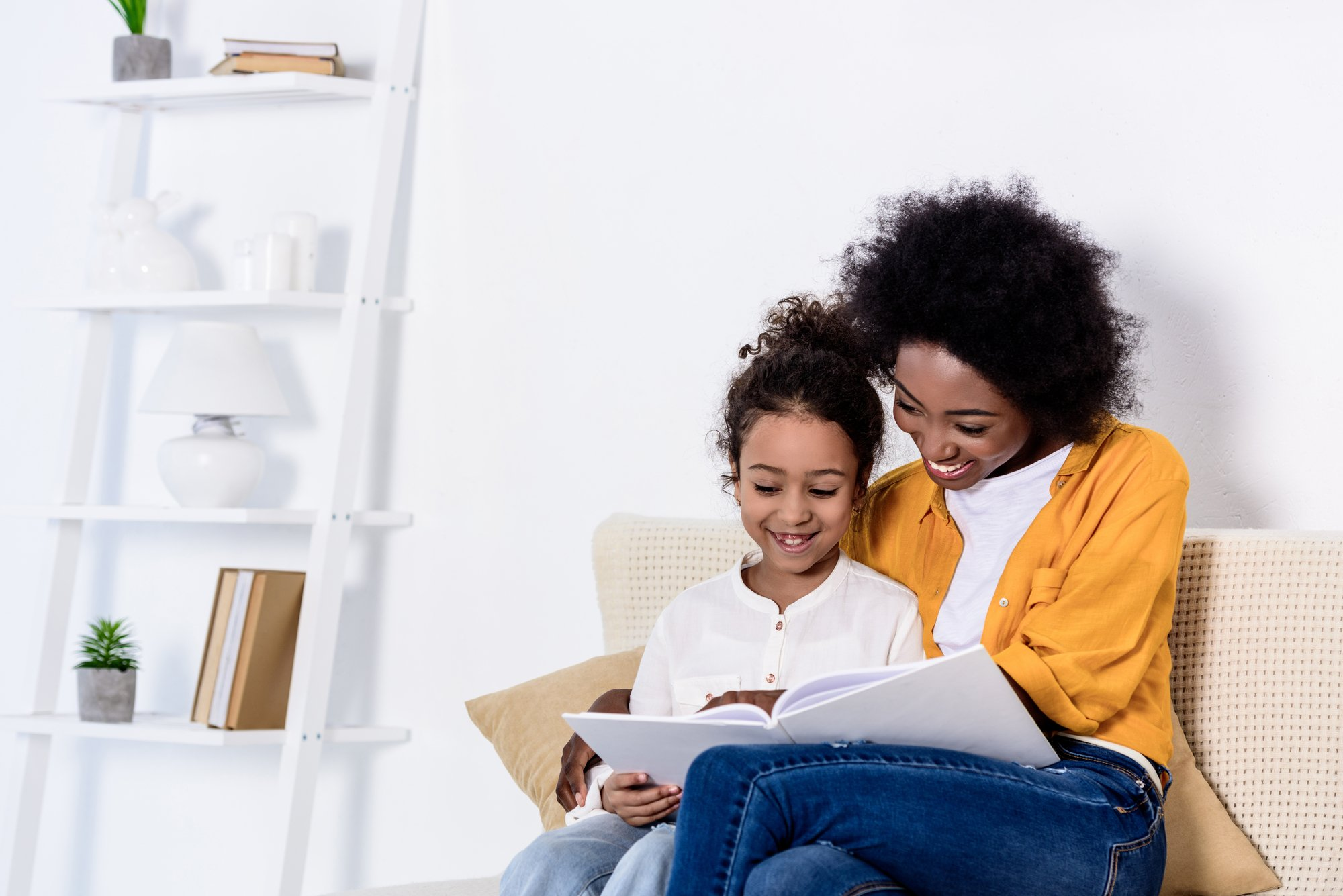 Happy african american mother and daughter reading book together at home
