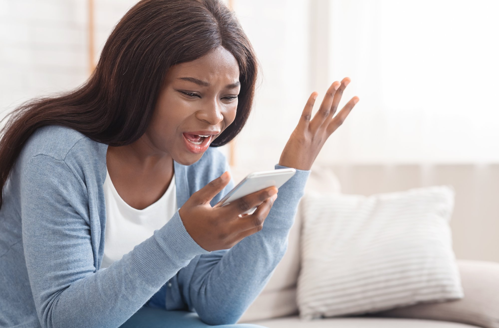 Portrait of young black woman shouting at mobile phone at home