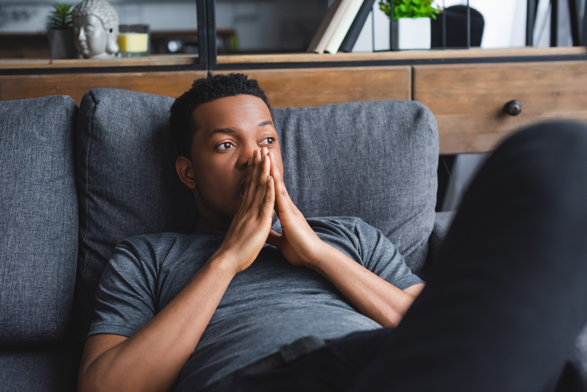 Sad thoughtful african american man lying on sofa at home
