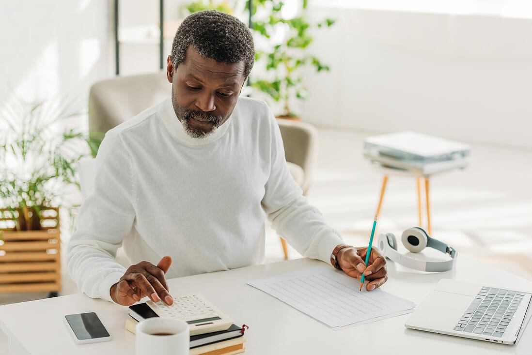 Serious african american man sitting at table near utility bill and calculating expenses