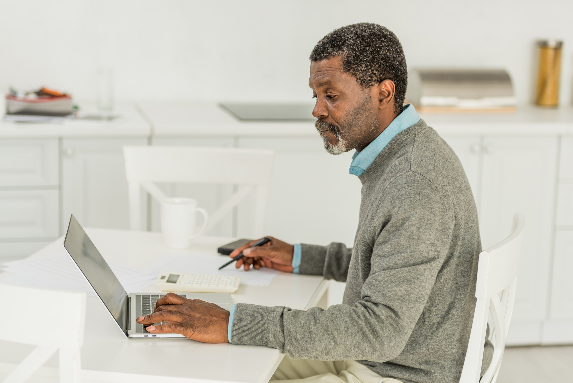 Serious african american man using laptop while calculating expenses
