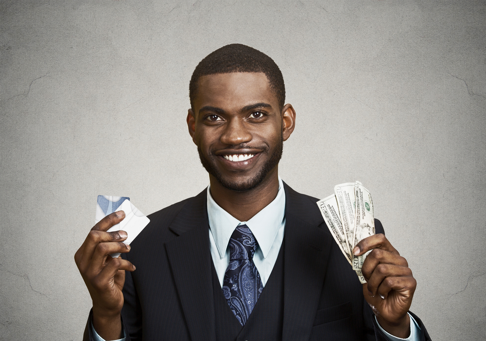 Closeup portrait happy, smiling business man company employee standing, holding dollar bills, credit card hand isolated grey black background. Banking exchange rate concept. Facial expression reaction