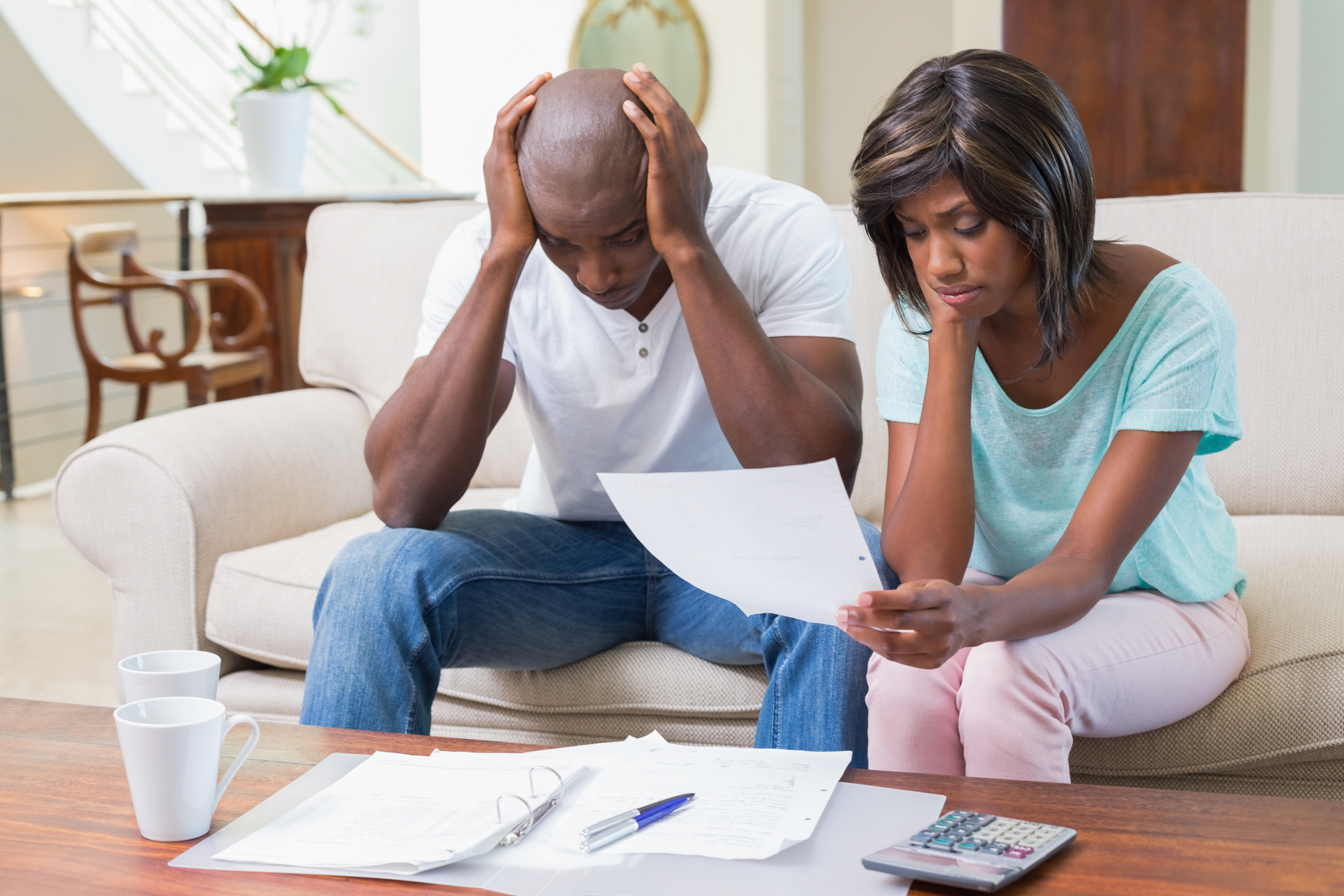 Stressed couple calculating bills on the couch