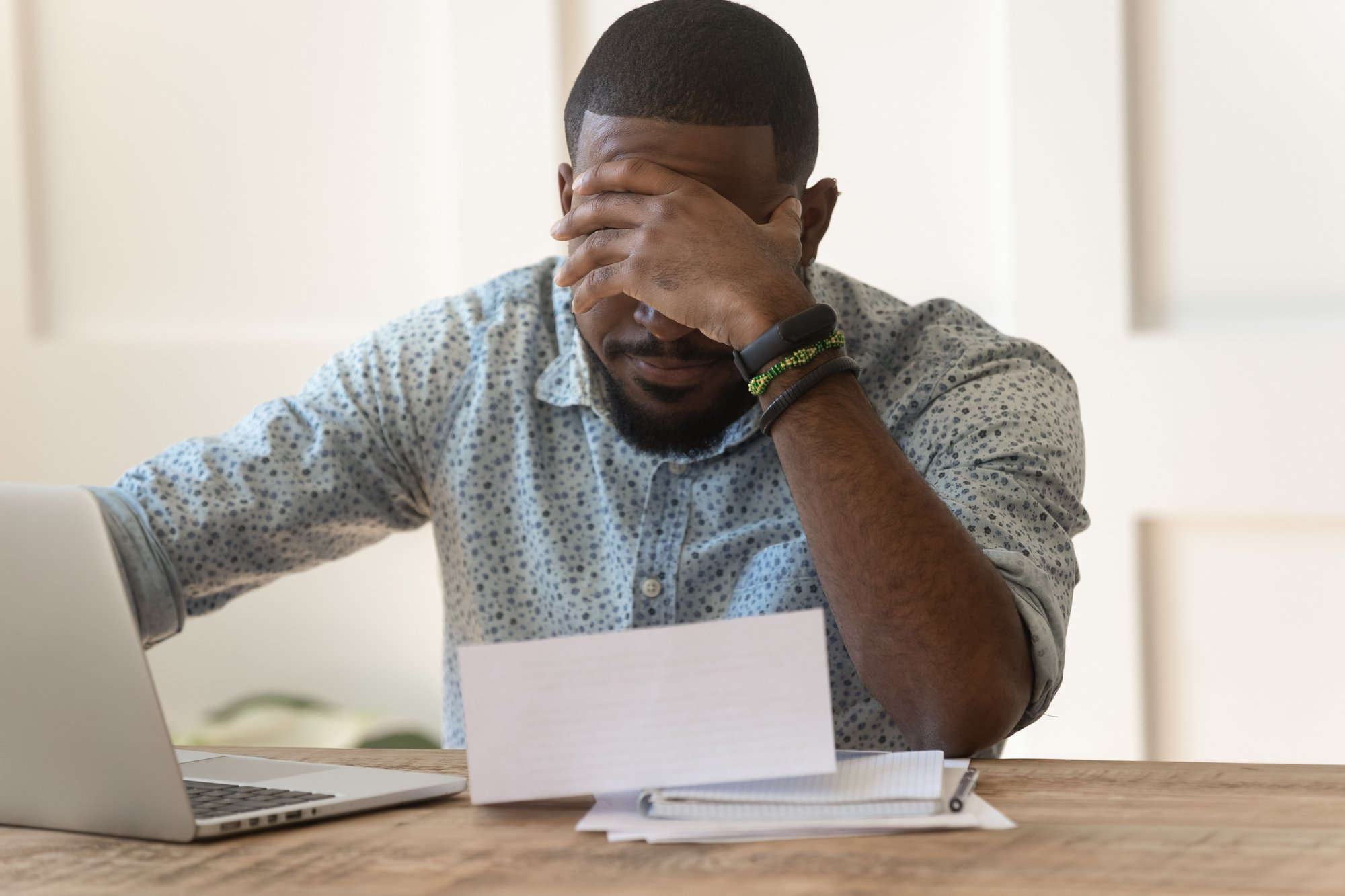 Stressed upset african american reading bad news in letter
