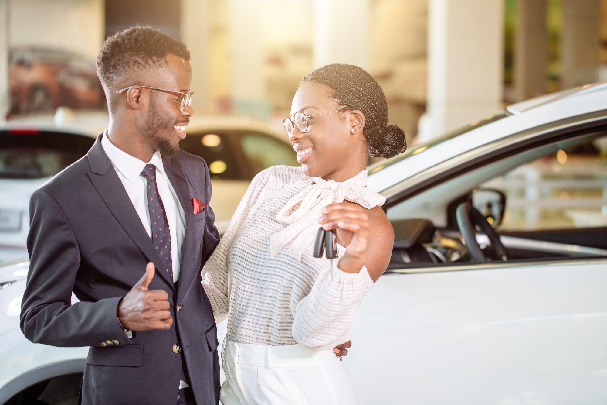 Visiting car dealership. couple holding key of their new car, looking at camera