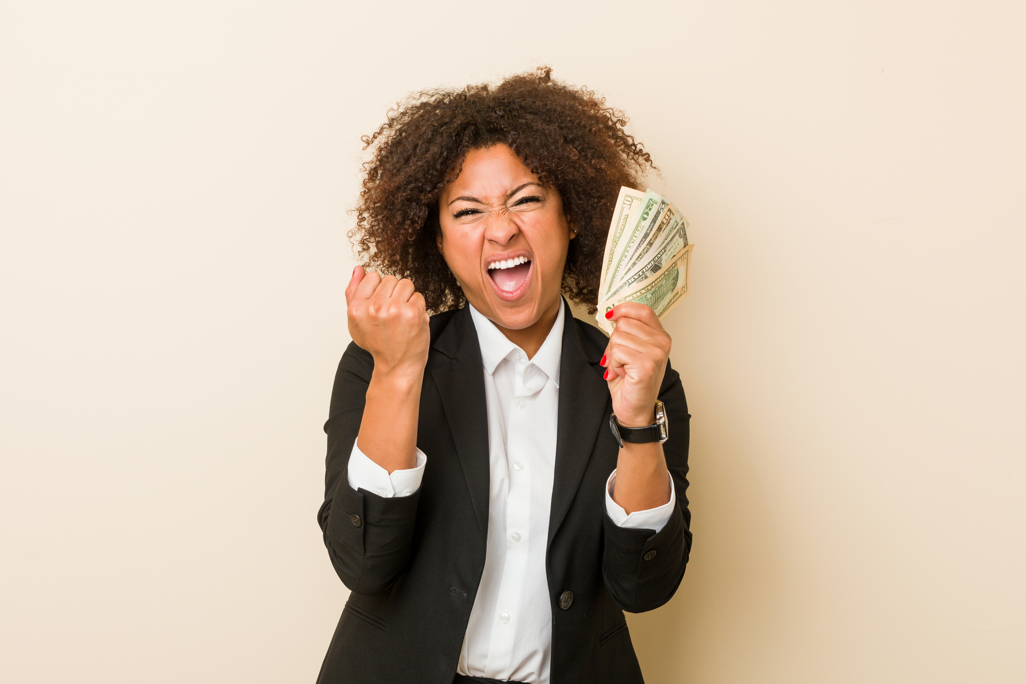 Young african american woman holding dollars cheering carefree and excited Victory concept